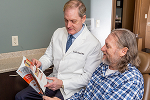 Dr. Nelson shows a patient a brochure.