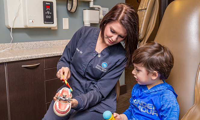 Dental hygienist shows a young child how to brush their teeth.