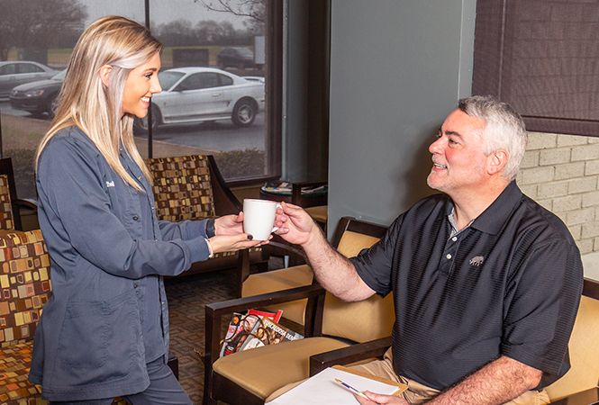 Receptionist hands a patient a cup of coffee.