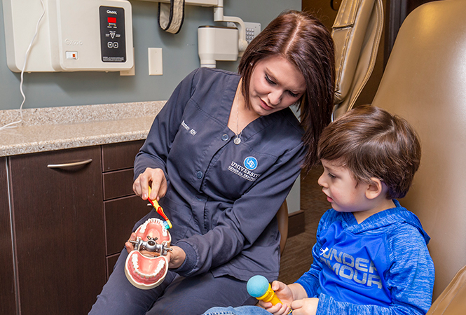 Hygienist shows a child how to properly brush his teeth.